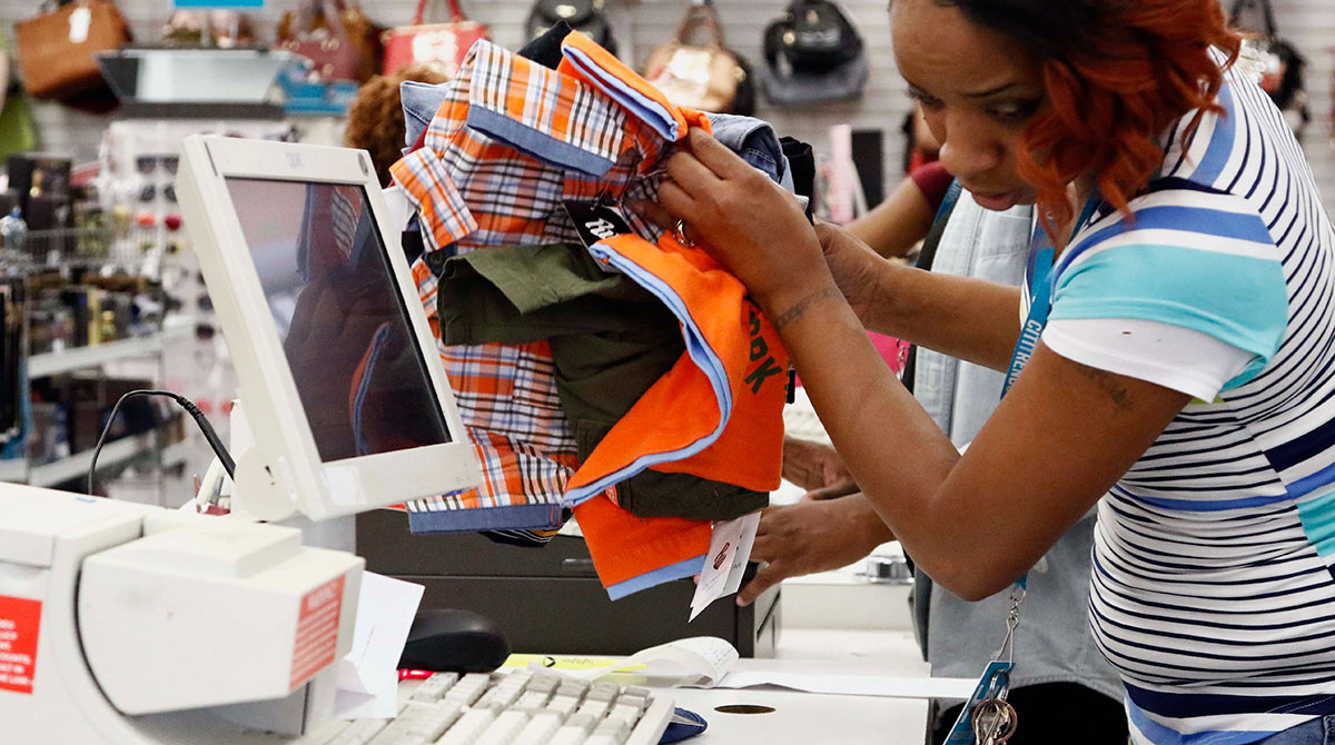 Citi Trends manager Crystal Bowman counts a customer's school clothes and uniforms in Jackson, Miss. (