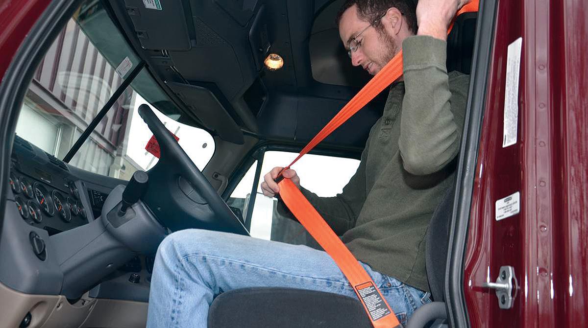 Truck driver puts on seat belt