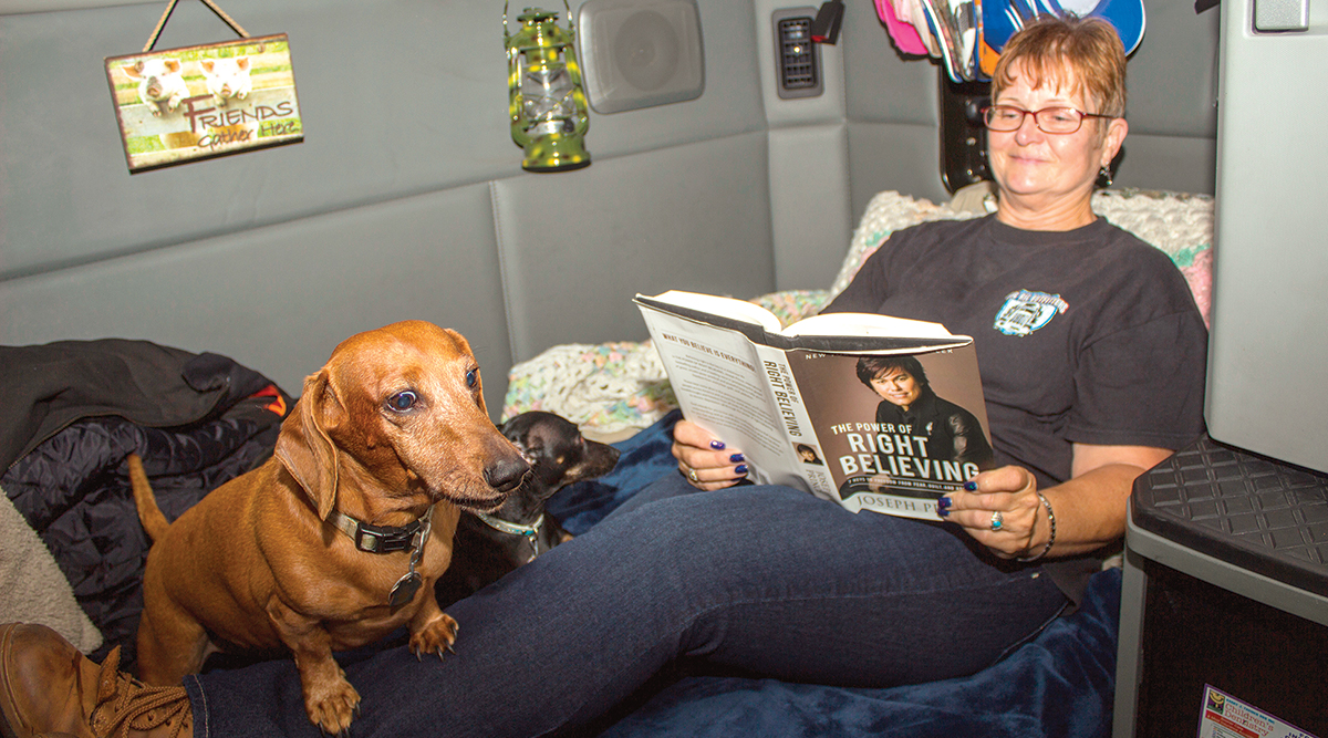 Woman reading with dog in sleeper berth