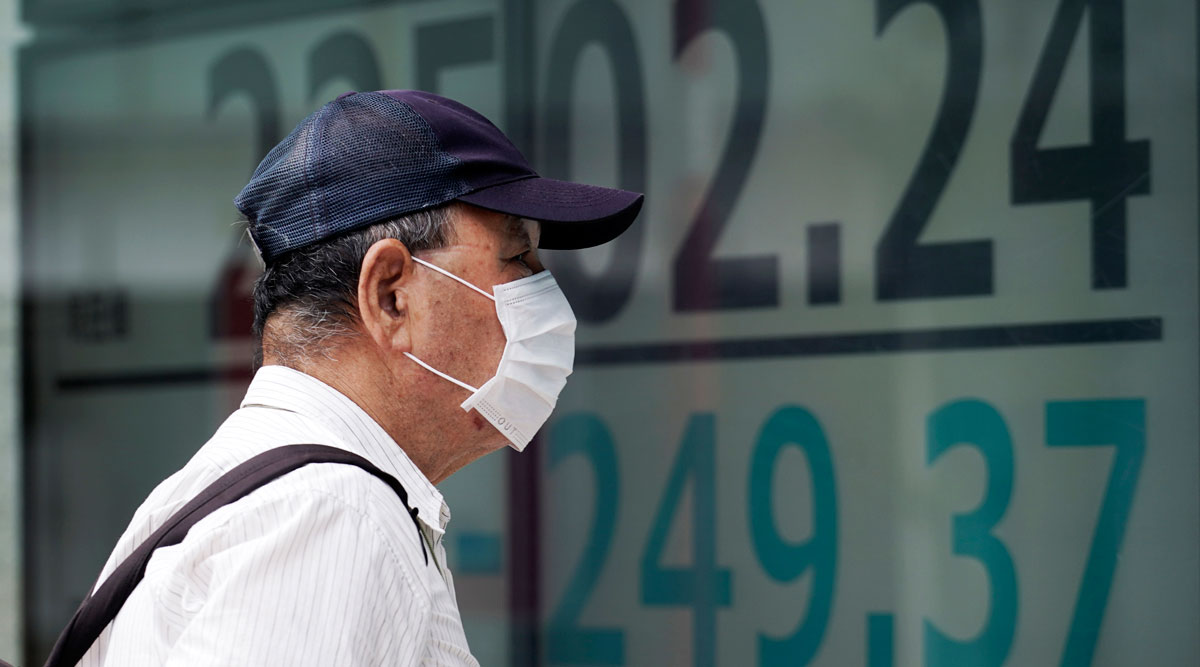 A masked man looks at an electronic stock board in Tokyo on July 27.