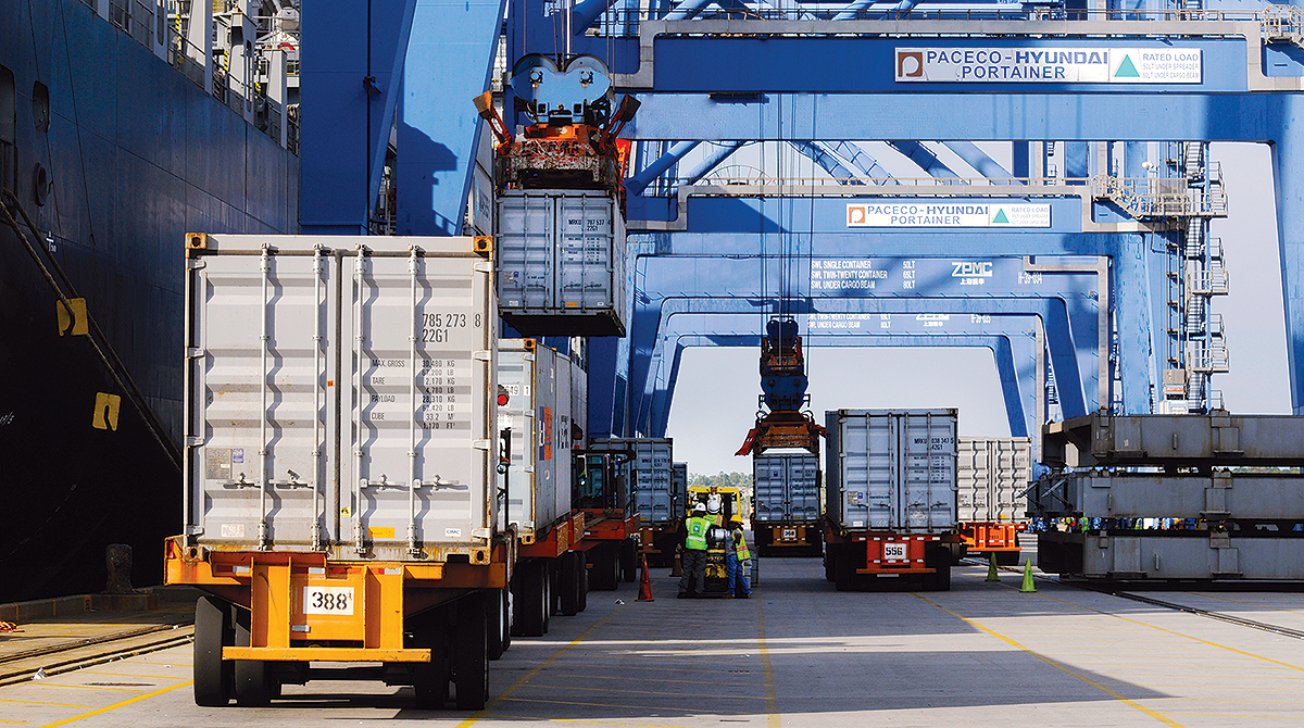 Trucks arrive with containers to be loaded onto a ship at the Port of Charleston