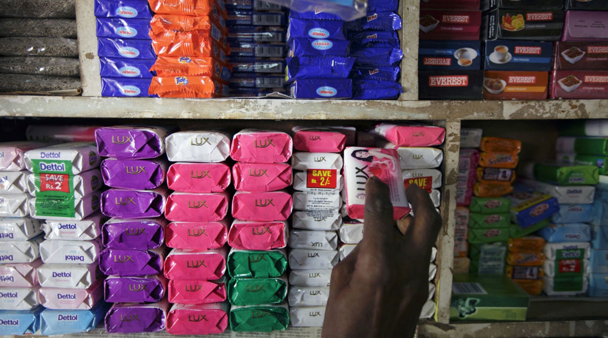 A man takes a bar of soap off a store shelf in Mumbai, India.