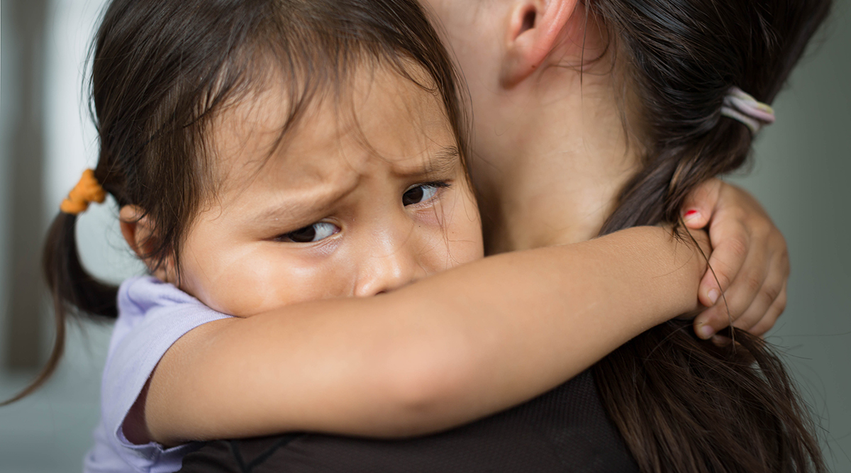 A crying child is comforted by her mother