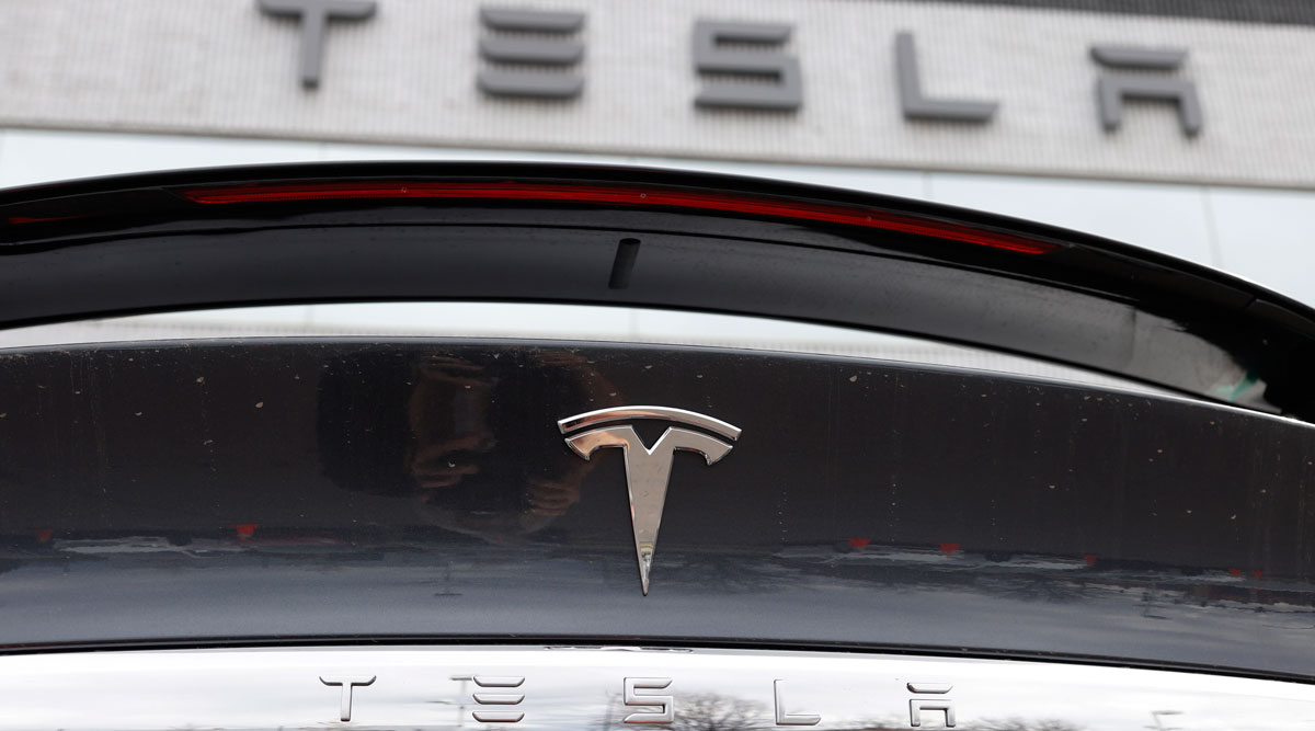 The Tesla company logo is seen on teh rear deck of an unsold 2020 Model X at a dealership.