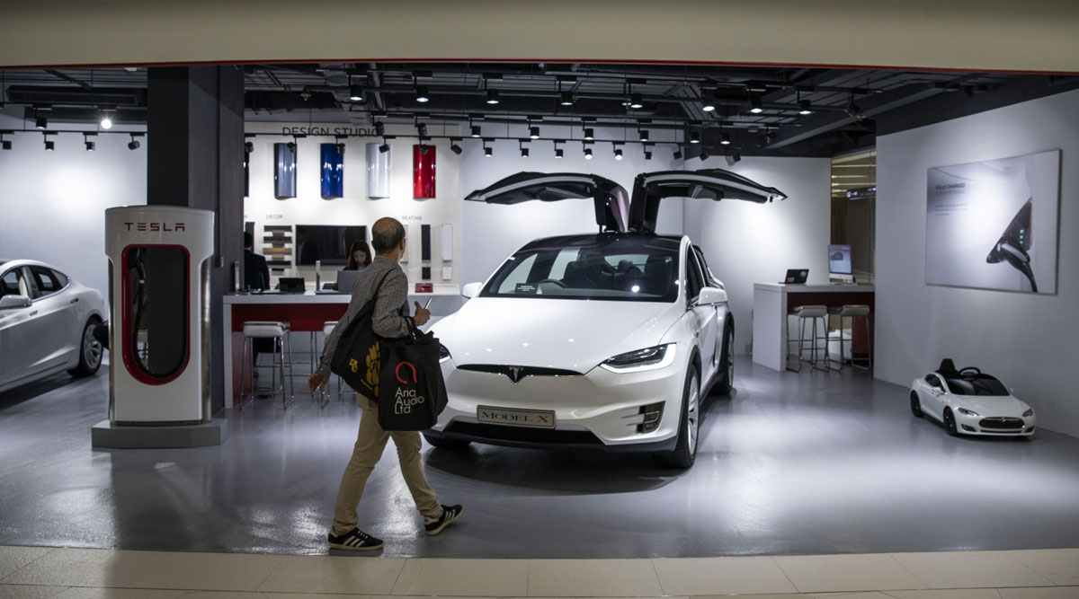 A man walks past a Tesla Model X electric vehicle on display at a showroom in Hong Kong.