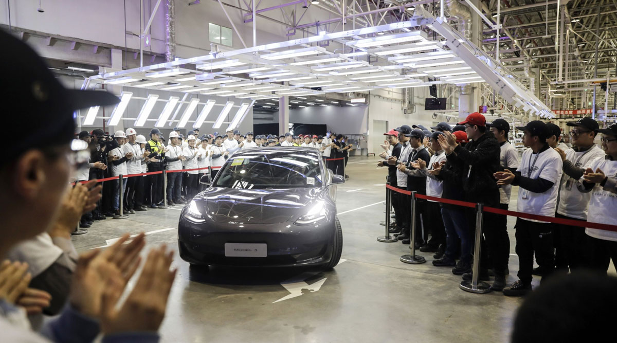 A Tesla Model 3 moves off an assembly line during a ceremony.