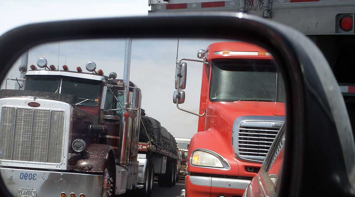 Trucks on a highway, reflected