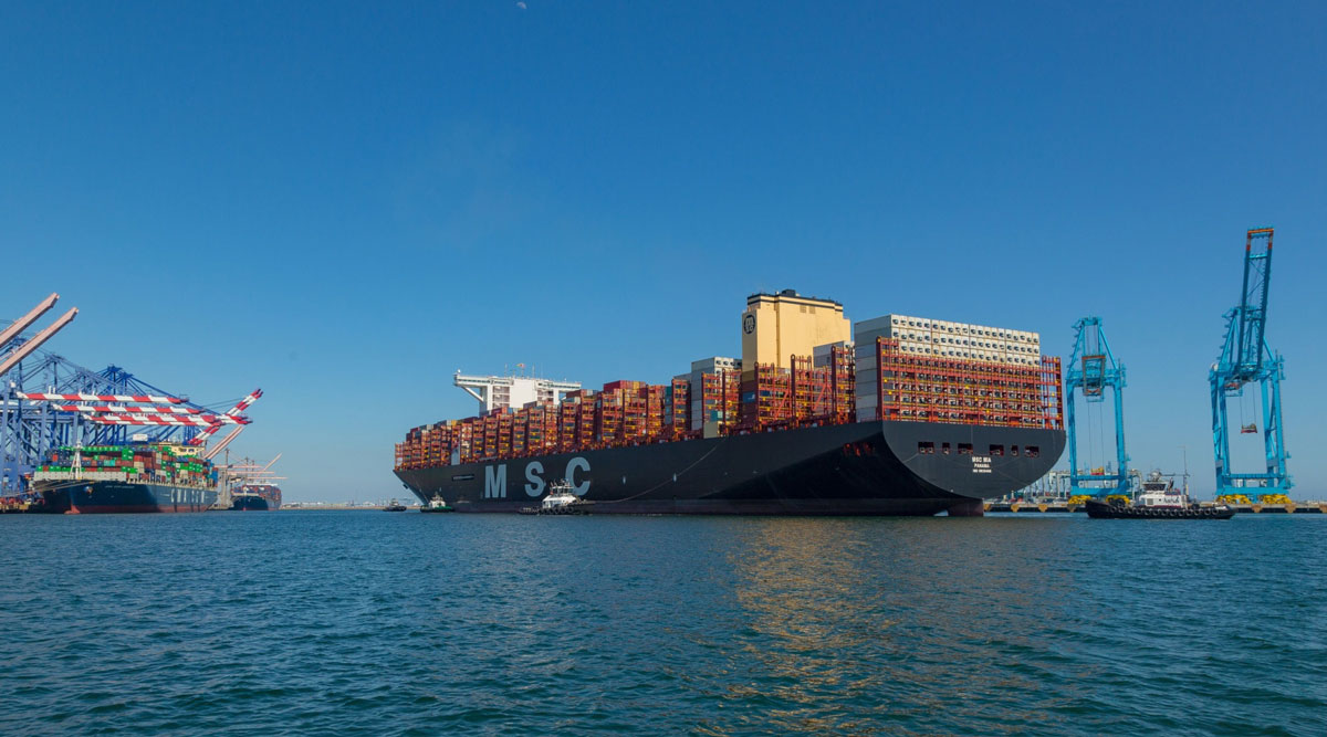 Tugboats guide a container ship arriving at the Port of Los Angeles on April 1.