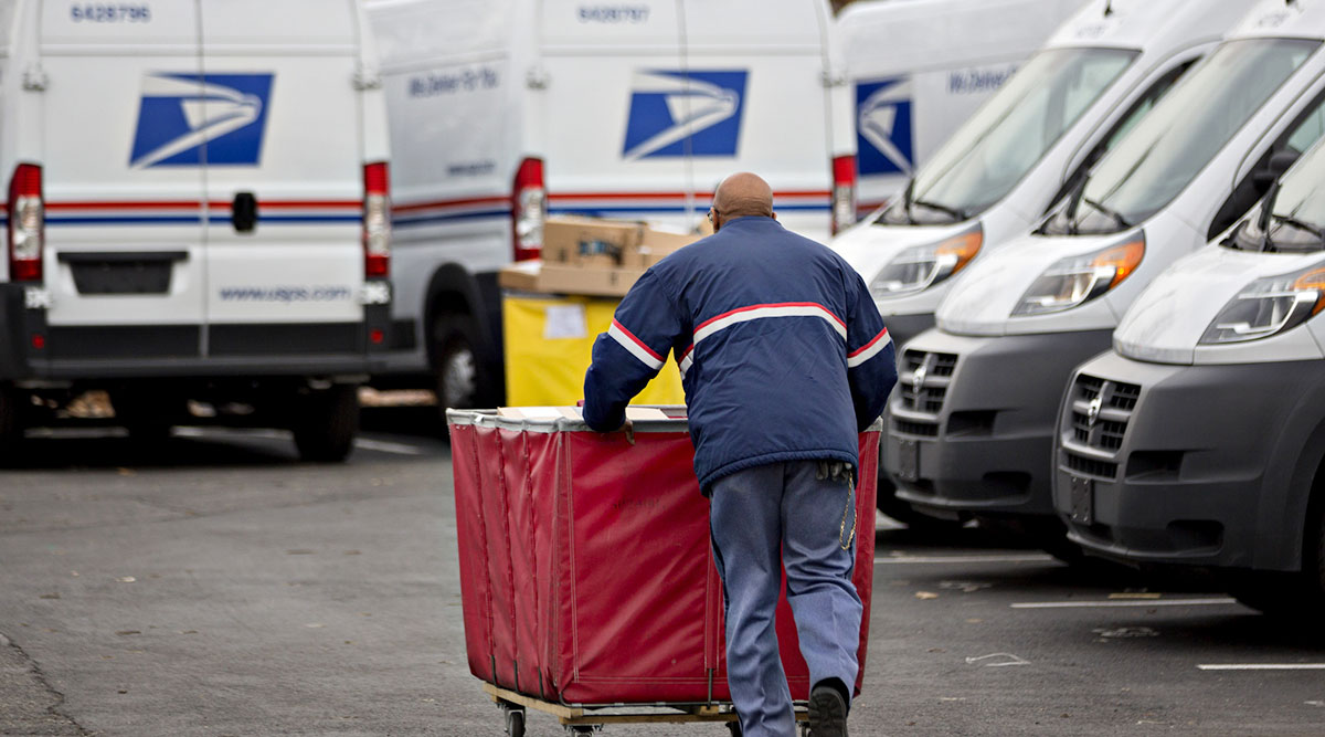USPS mail truck and delivery driver