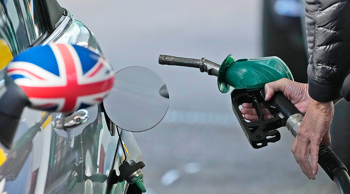 A driver fills a car with fuel at a petrol station in London