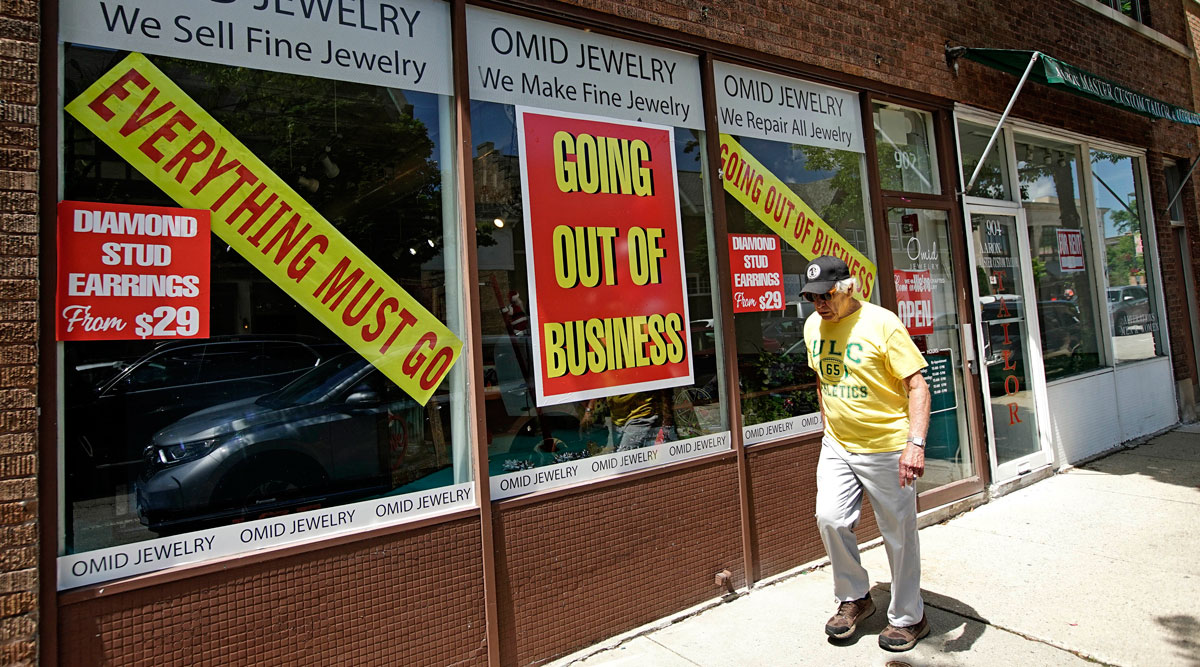 A man walks past an Illinois retail store going out of business due to the pandemic on June 23.