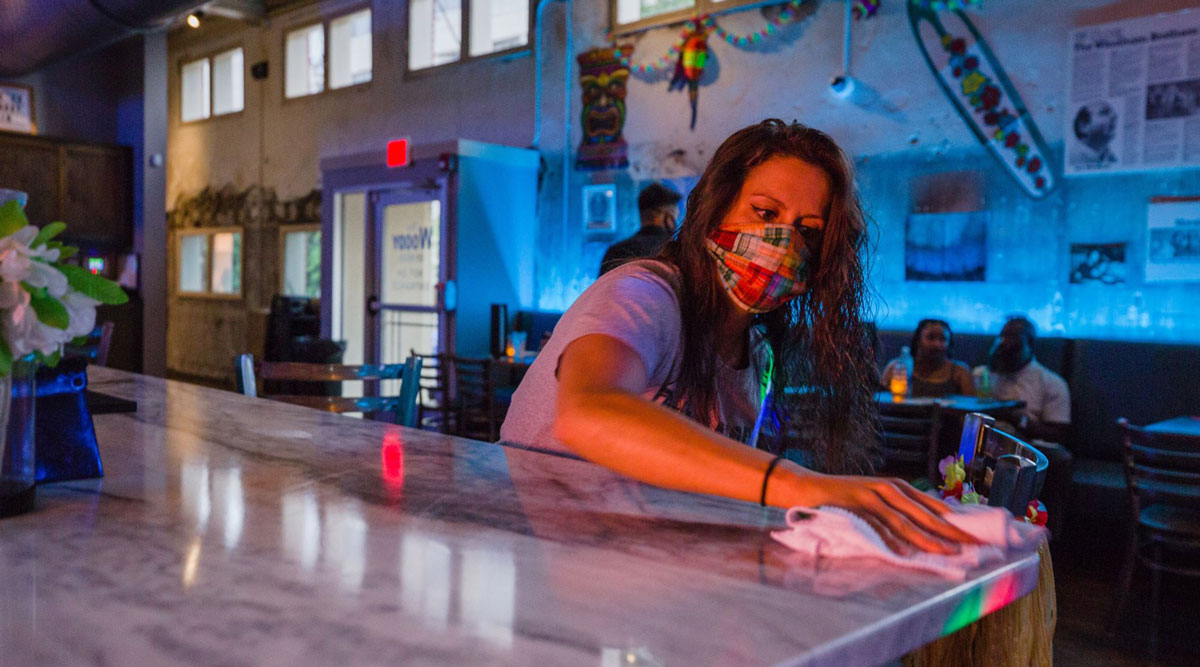 A worker disinfects a bar at a nightclub in South Carolina.