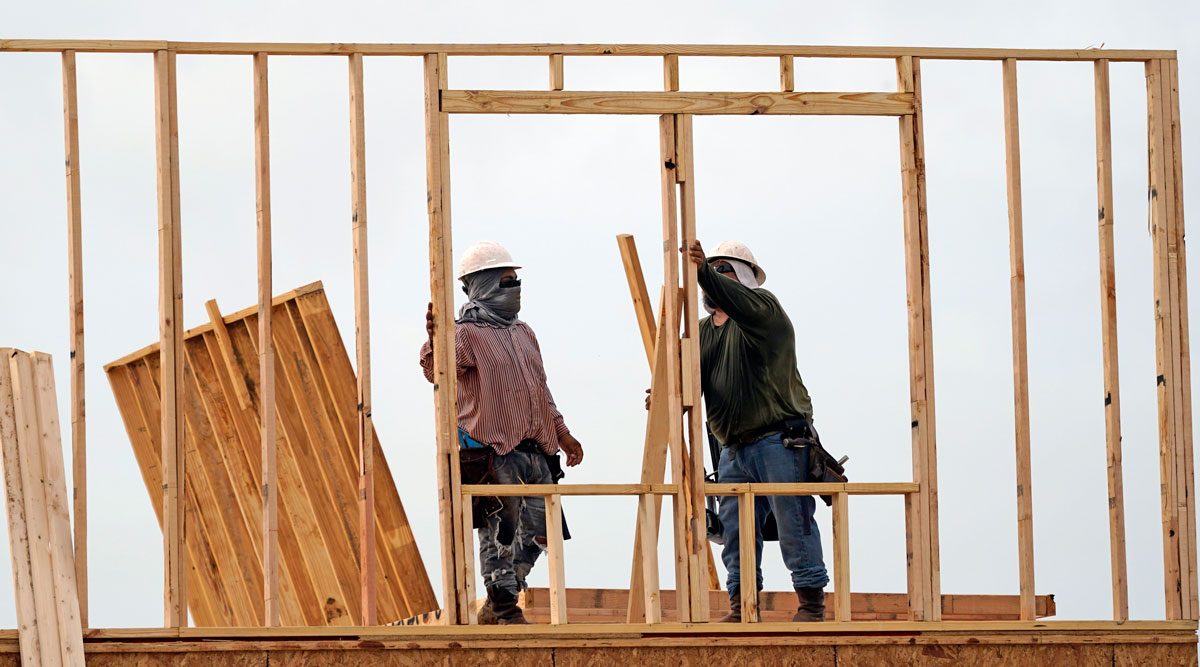 Construction workers build a new home in Houston on June 23.