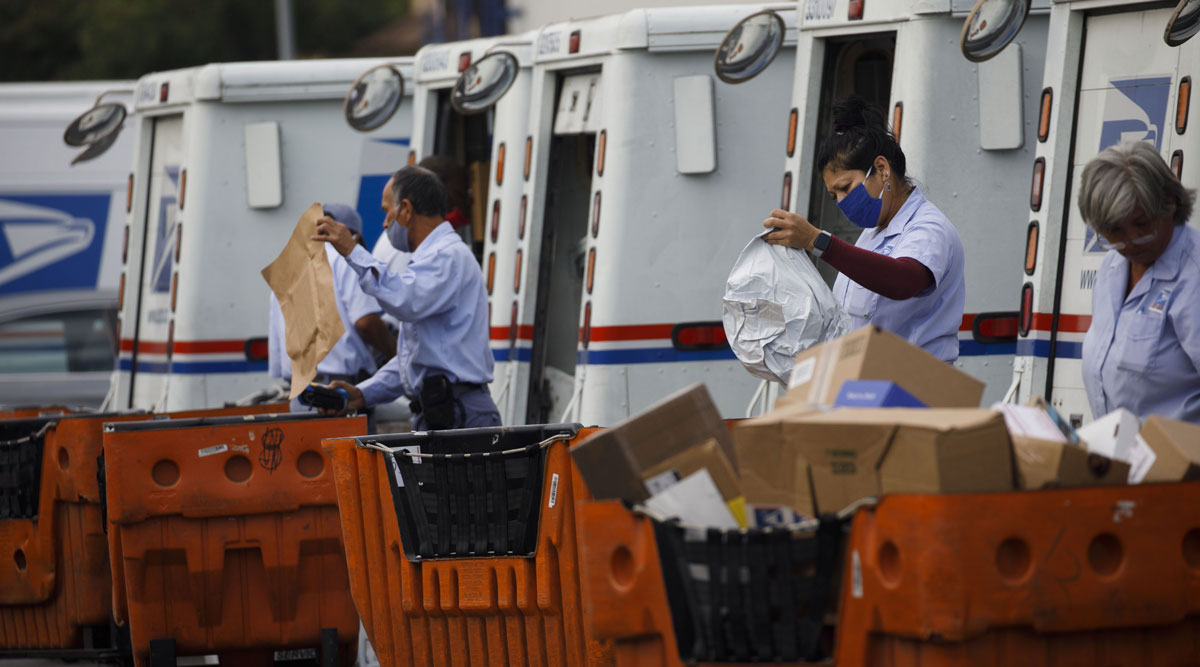 USPS employees load mail into delivery vehicles in Torrance, Calif., on Aug. 17.