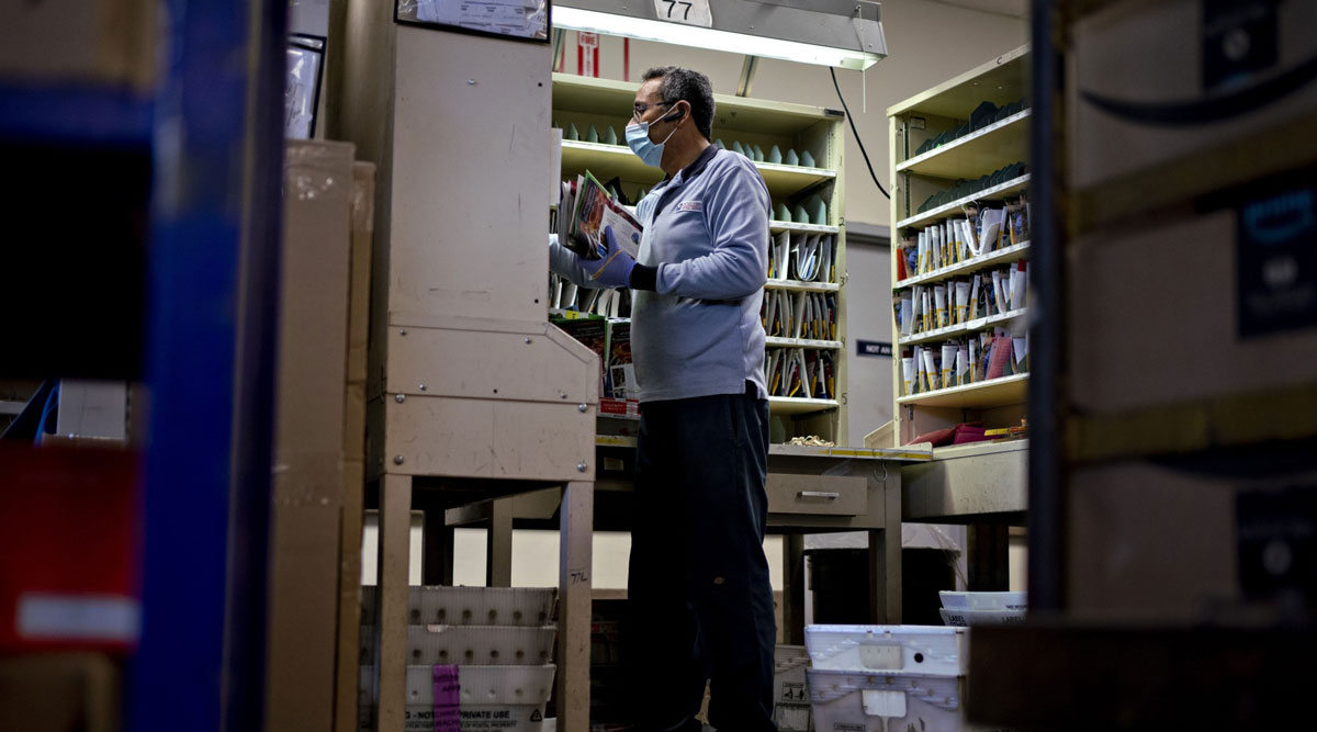 A letter carrier prepares mail for delivery at a USPS facility in Virginia.