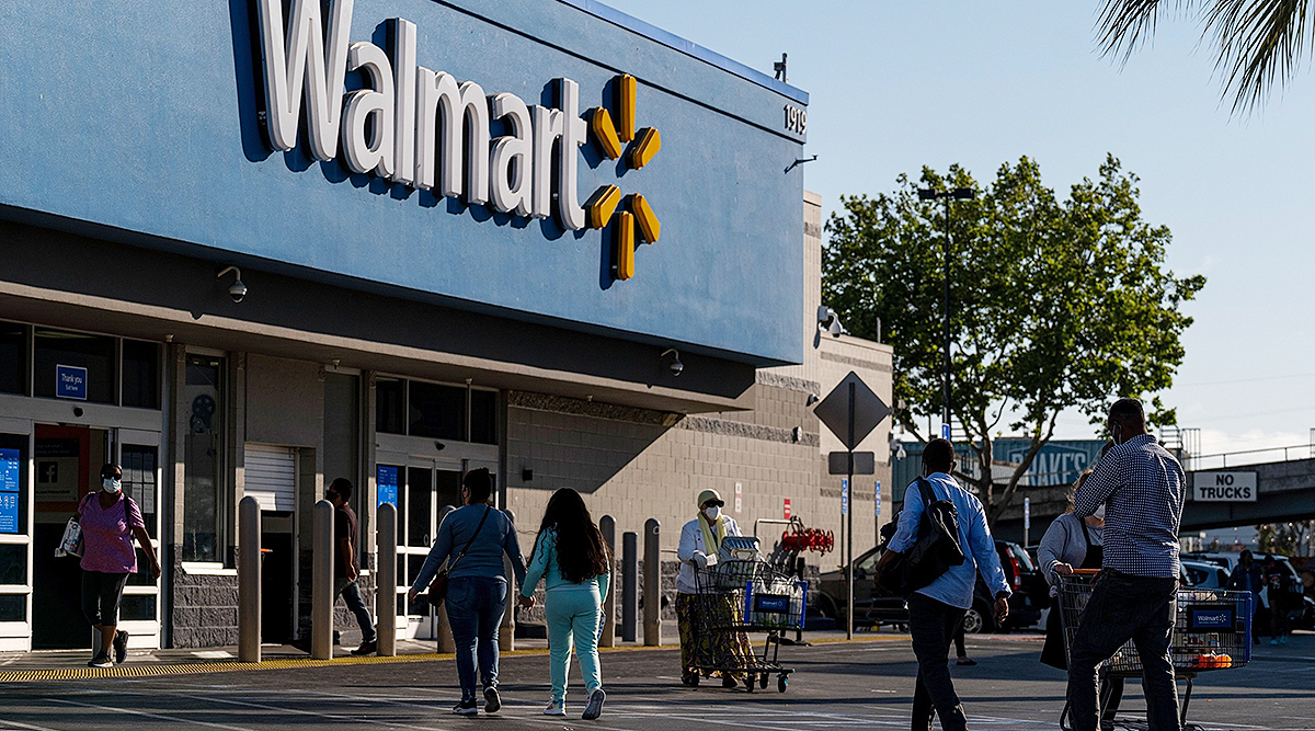 Shoppers walk in front of a Walmart store in San Leandro, Calif.