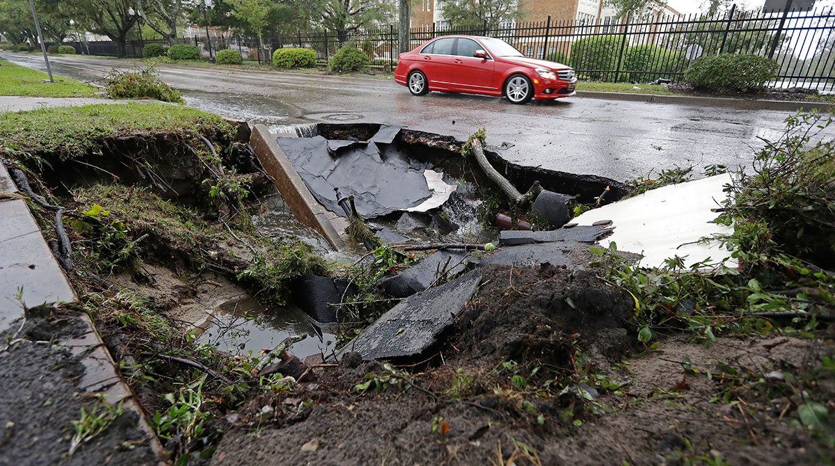 A car drives past a sinkhole in Wilmington, N.C.