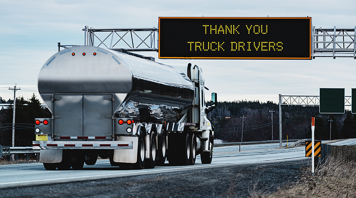 Truck passing under sign thanking truck drivers on road
