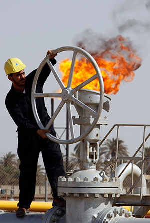 Iraqi oil worker operates valves