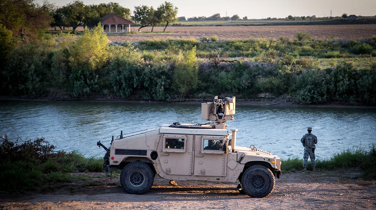 A soldier from the 36th Infantry Division, Texas Army National Guard observes a section of the Rio Grande River at sunset