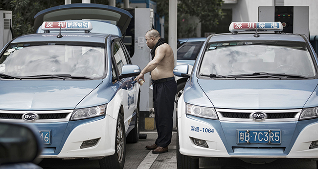 A driver charges his electric-powered taxi in Shenzhen