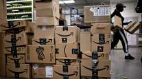 Amazon boxes sit stacked at a USPS facility in Fairfax, Va., on May 19. (Andrew Harrer/Bloomberg)