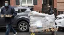 A worker carries Amazon packages during a delivery in New York.