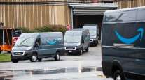 Vans leave an Amazon delivery station in Carlstadt, N.J. (Michael Nagle/Bloomberg News)