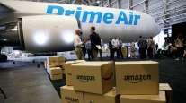 "Amazon boxes stacked near a an Amazon ""Prime Air"" cargo plane in Seattle"