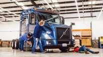 Workers clean an autonomous Embark truck