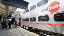 Commuters board a Caltrain car at the transit station in Millbrae, Calif.