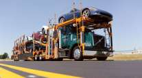 A Jack Cooper truck transports cars down a highway.