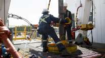 Employees torque a pipe at a wedge well at Cenovus Energy's Christina Lake in situ oil production facility in Conklin, Alberta, Canada.