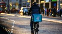 A Deliveroo food carrier cycles along Oxford Street in central London