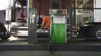 Trucker pumping diesel into purple truck