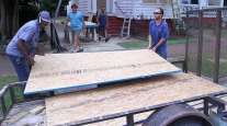 Workers prepare to install plywood panels on a house in New Bern, N.C.