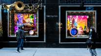 Pedestrians walk past holiday windows display at the Bloomingdale's Inc. store in New York.