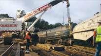A Cranemaster crane rerails some railcars.