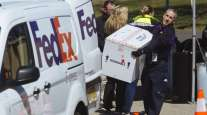 A FedEx employee carries a box before loading into a van at a coronavirus testing facility in New Jersey.