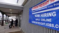 """A """"Now Hiring"""" sign hangs on the front wall of a Harbor Freight Tools store in New Hampshire."""