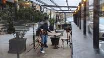 A worker removes chairs from the outdoor dining tent of a restaurant in New York. (Angus Mordant/Bloomberg News)