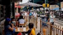 Pedestrians pass in front of restaurant customers in the Queens borough of New York.
