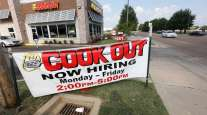 Cars drive by a help wanted sign at a Cook Out restaurant in Jackson, Miss.