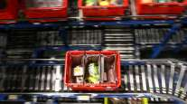 A customer order crate travels along a conveyor belt at the Ocado Group Plc distribution center in the United Kingdom.