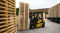 An employee uses a forklift truck to move a stack of heat-treated wooden pallets. (Chris Ratcliffe/Bloomberg News)
