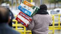 A shopper carries paper towels and toilet paper from a Costco