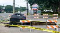 Ocala, Fla, - June 11, 2017: A sinkhole opens in a parking area and swallows a car that teeters on the edge.