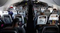 Passengers wear protective masks on an American Airlines flight. (Patrick T. Fallon/Bloomberg News)