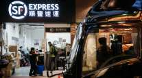 Employees handle packages at an SF Express store in Hong Kong. (Anthony Kwan/Bloomberg News)