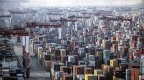 Shipping containers sit next to gantry cranes at the Yangshan Deepwater Port in Shanghai, China, on Jan. 11.